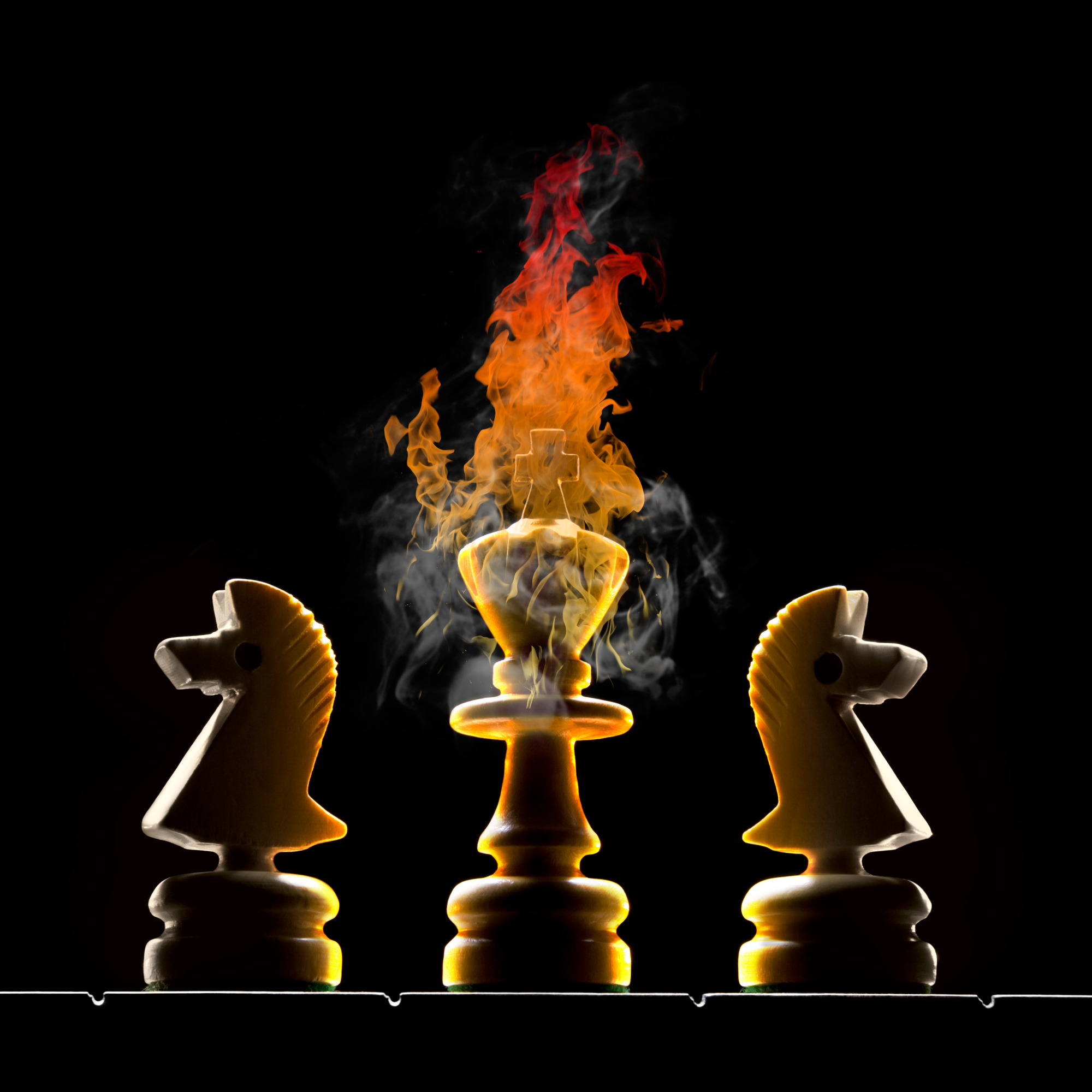 Chessmen (king and two horses). King burns on a black background.