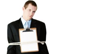 Handsome businessman standing with a clipboard with blank paper on his chest and his arms securely tied to his sides by a rope conceptual of being bound by the restrictive regulations of bureaucracy